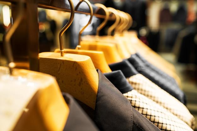 Garnitury męskie wiszące w sklepie odzieżowym.