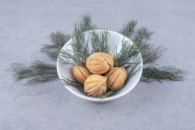 Garść ciastek z karmelem ozdobionych liśćmi sosny na marmurowym stole.
