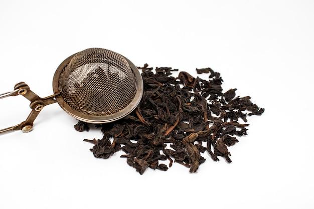 Garść liści czarnej herbaty na białym tle. napój jest niezastąpiony, gdy trzeba się rozgrzać, ale doskonale sprawdza się również w upale.