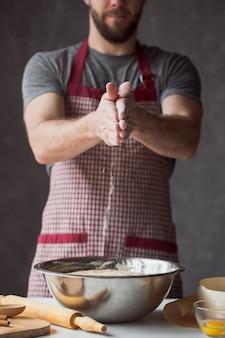 Garść mąki z jajkiem na rustykalnej kuchni. na stole męskich rąk ugniatamy ciasto