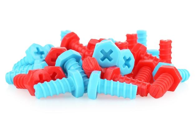 Garść plastikowych śrubek dla dzieci w różnych kolorach na białym tle.