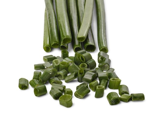 Garść posiekanej zielonej cebuli i łodyg cebuli na tle, na białym tle.