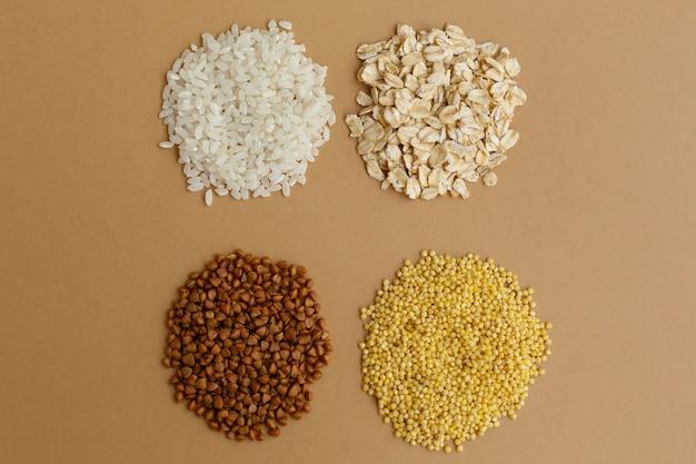 Garść różnych zbóż na brązowym tle. ryż i płatki owsiane, kasza gryczana i proso