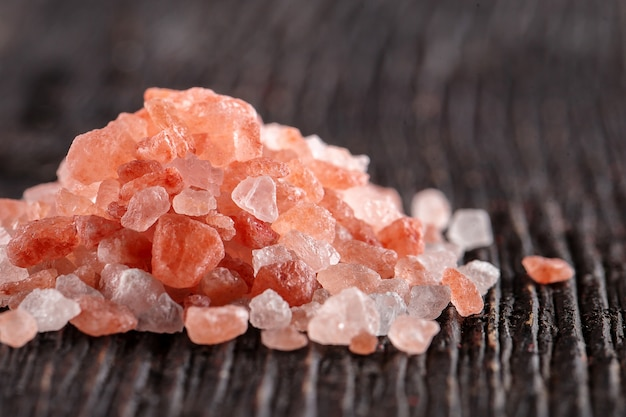 Garść różowej himalajskiej soli krystalicznej na ciemnym drewnianym stole