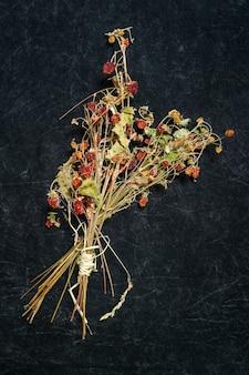 Garść suszonych truskawek na czarnej powierzchni.