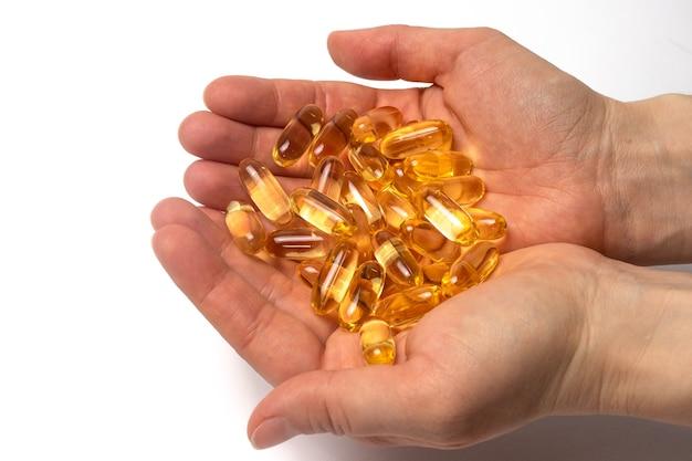 Garść żółtych kapsułek omega-3 w ludzkich rękach.
