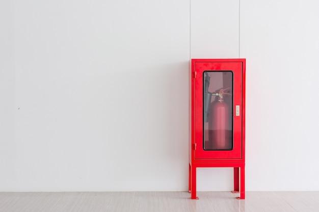 Gaśnica w czerwonym gablocie na ścianie do ochrony przeciwpożarowej w fabryce