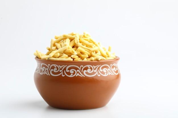Gathiya to bardzo popularna przekąska gudżarati w brązowej misce na białej powierzchni