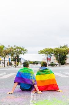 Gay z flagami tęczy siedzi na ulicy