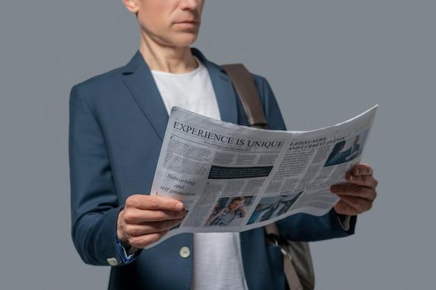 Gazeta, aktualności. mężczyzna w kurtce, z torbą na ramieniu, z gazetą w dłoni, czytający najnowsze wiadomości, widoczna dolna część twarzy