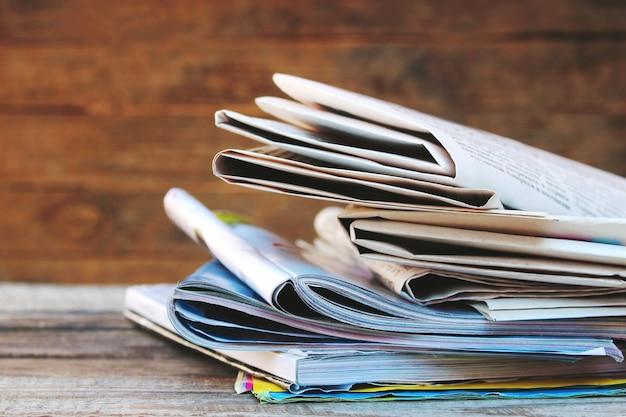 Gazety i czasopisma na starym stole z drewna