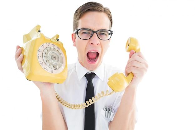 Geeky biznesmen krzyczy przy retro telefonem