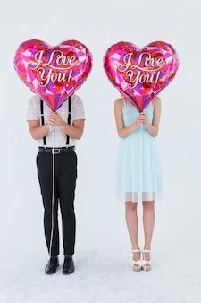 Geeky hipster para z balonami przed ich głową