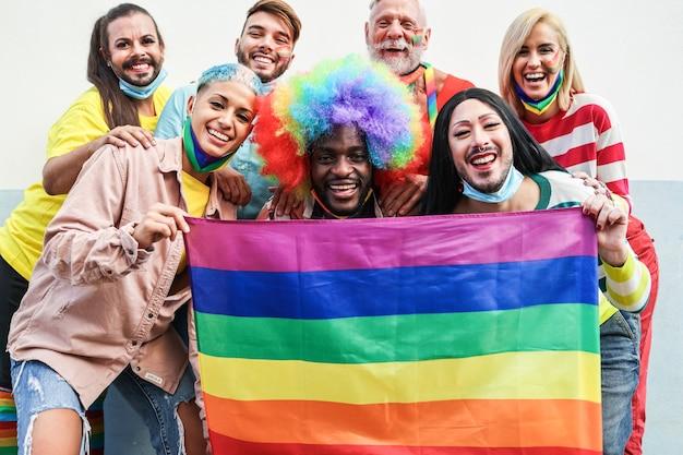 Geje tańczą na paradzie dumy z flagami lgbt, nosząc ochronną maskę na twarz