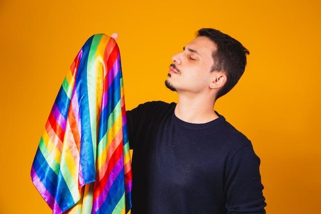 Gejowska duma. homoseksualny chłopiec całuje flagę lgbt na żółtym tle.