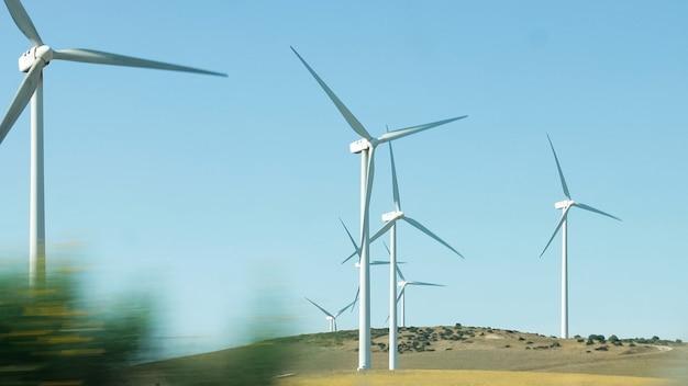 Generatory wiatrowe obracające się podczas pracy widziane z jadącego samochodu