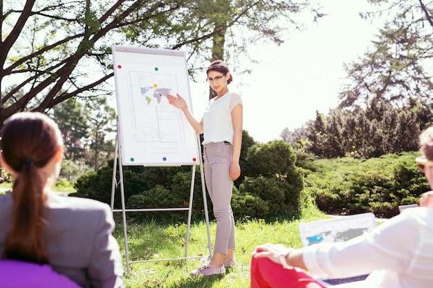Generowanie pomysłów. poważna stylowa dziewczyna stojąca przy tablicy i omawiająca swój projekt z kolegami z grupy