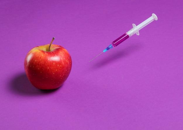 Genetycznie zmodyfikowane czerwone jabłko ze strzykawkami na fioletowo, koncepcja owoców minimalna