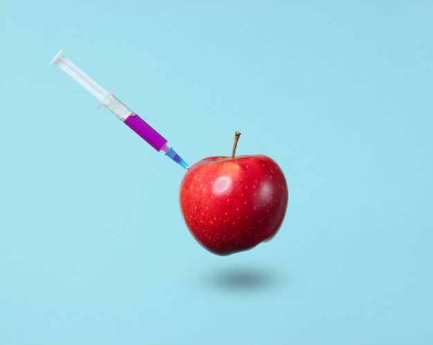 Genetycznie zmodyfikowane czerwone jabłko ze strzykawkami na niebiesko.