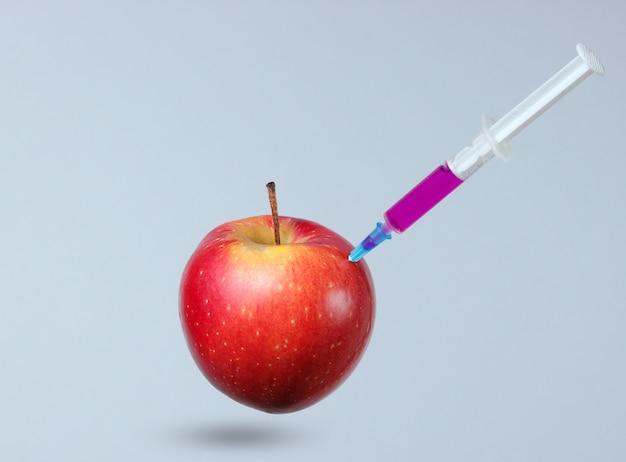 Genetycznie zmodyfikowane czerwone jabłko ze strzykawkami na szaro.