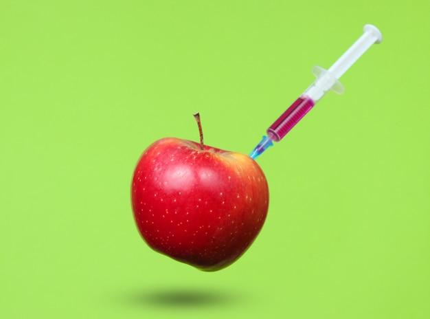 Genetycznie zmodyfikowane czerwone jabłko ze strzykawkami na zielono.