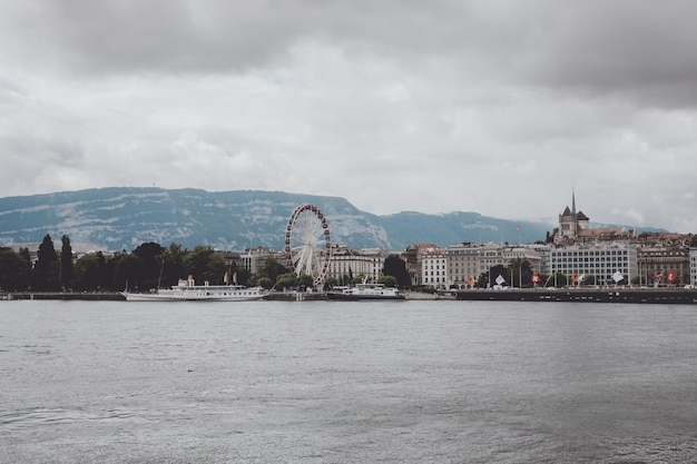 Genewa, szwajcaria - 1 lipca 2017 r.: widok na jezioro genewskie, odległe góry i miasto genewa, szwajcaria, europa. letni krajobraz, słoneczna pogoda, dramatyczne zachmurzone niebo