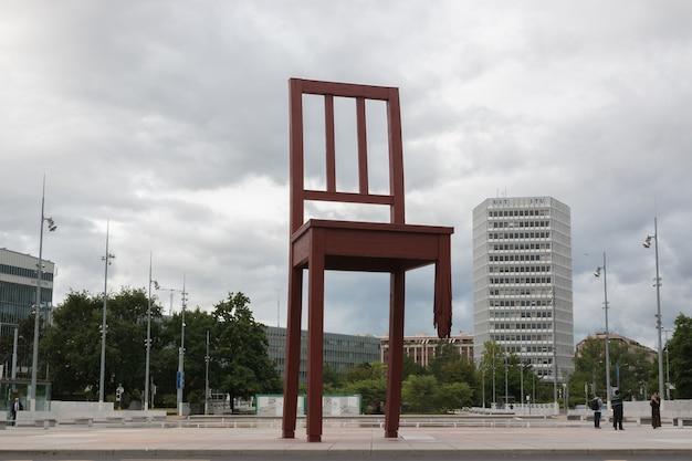 Genewa, szwajcaria - 1 lipca 2017: złamane krzesło na placu narodów w genewie w piękny letni dzień z dramatycznym niebem, szwajcaria, europa