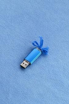 Genialna niebieska karta pamięci flash usb z niebieską kokardą leży na kocu z miękkiej, futrzanej, jasnoniebieskiej tkaniny polarowej.