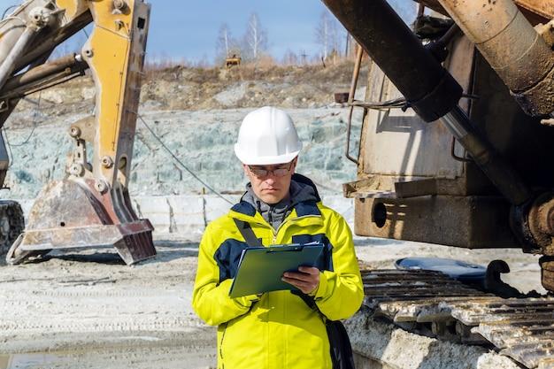 Geolog lub inżynier górnictwa pisze coś w mapniku pośród kamieniołomu ze sprzętem budowlanym