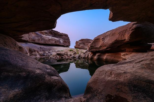 Geologiczna jaskinia dziur w dużych skalistych bystrzach i odbicie w stawie wieczorem w sam phan bok