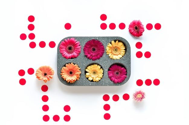 Geometryczna kompozycja, żywe kwiaty gerbera i okrągłe papierowe kółka wokół prostokątnej formy do pieczenia.