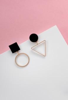 Geometryczne kolczyki na białej i różowej powierzchni z miejsca kopiowania