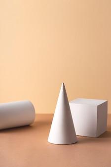 Geometryczne kształty w kolorze białym - cylinder, sześcian i stożek