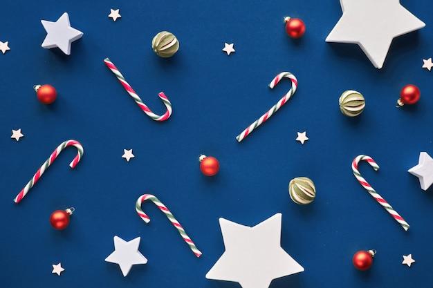 Geometryczne święta na modnym niebieskim papierze. modne geometryczne świąteczne mieszkanie leżało, widok z góry z cukierkami, liśćmi ostrokrzewu i gałązkami jodły, drewnianymi gwiazdami i szklanymi bibelotami. wesołych ferii zimowych!