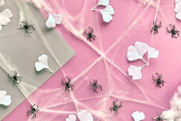 Geometryczne tło halloween z białymi liśćmi miłorzębu, pajęczyną i pająkami na różowym i rzemieślniczym papierze.