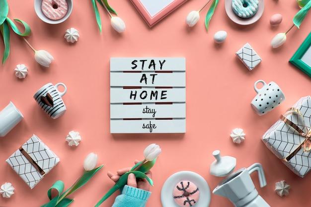 Geometryczne wiosenne mieszkanie leżało w kolorze białym i zielonym na różowej ścianie wielkanoc, dzień matki, urodziny wiosny lub rocznica. plastikowa płyta grzewcza, pisanki, ekspres do kawy, filiżanki, tulipany, prezenty.