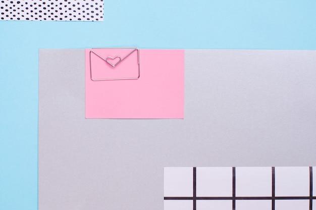 Geometryczny blok kolorów tło z pinezką koperty w kształcie serca z pustym miejscem na tekst. widok z góry, płaski układ.