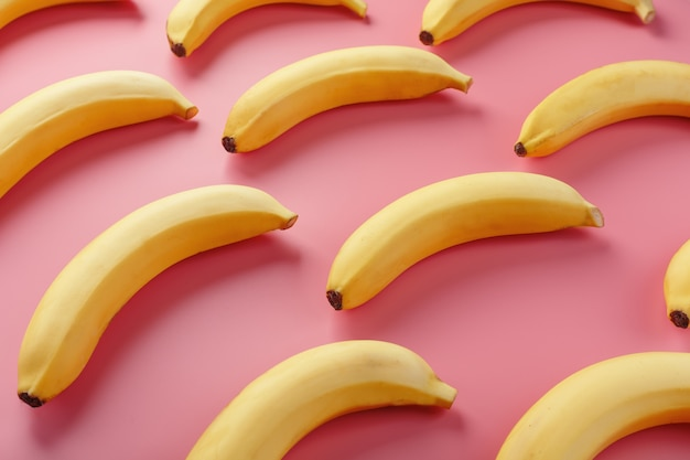 Geometryczny wzór bananów na różowym stole. widok z góry. minimalistyczny styl płaski. projektowanie w stylu pop, koncepcja kreatywnego lata.