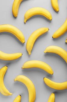 Geometryczny wzór żółtych bananów na szarym tle w modnych kolorach 2021 roku.