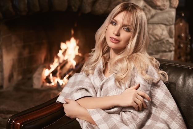 Georgeous elegancka blondynka pod jasną kratą przy kominku