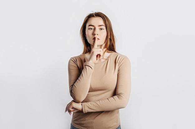 Gest ciii. młoda piękna poważna dziewczyna trzyma palec na ustach na białym tle na białym tle. kobieta prosi o milczenie, miejsce na reklamę. negatywna brunetka w beżowym swetrze.