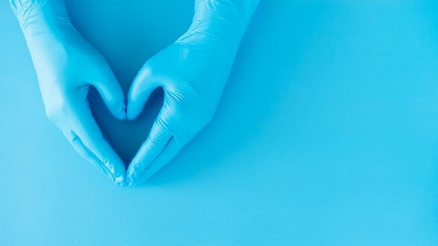 Gest dłoni lekarza na sobie niebieskie rękawiczki na niebiesko, znak kształt serca dla miłości