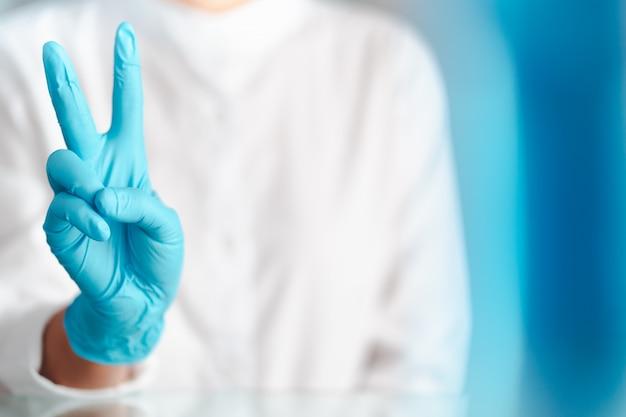 Gest dłoni lekarza w niebieskich rękawiczkach, znak do walki
