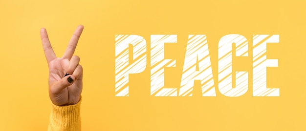 Gest dłoni znak v dla znaku zwycięstwa lub pokoju na żółtym tle, obraz panoramiczny