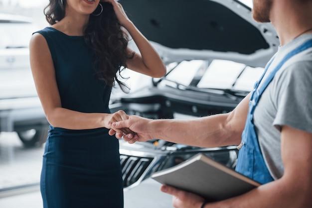Gest drżenie ręki. kobieta w salonie samochodowym z pracownikiem w niebieskim mundurze zabierająca naprawiony samochód z powrotem.