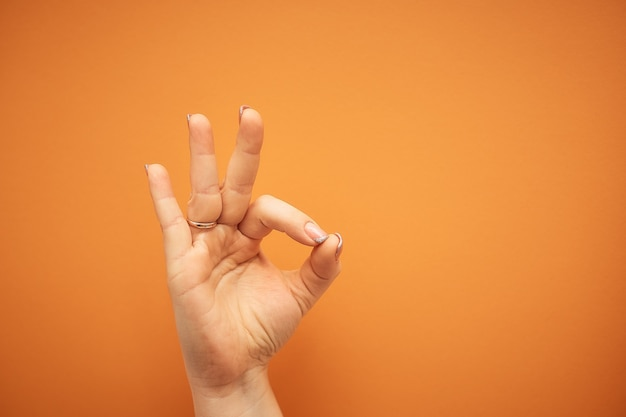 Gest, kobieca ręka pokazuje znak ok na pomarańczowym tle.