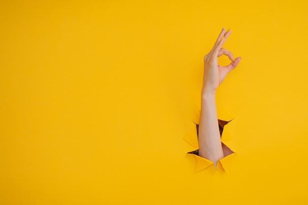 Gest kobiecej dłoni ok przez dziurę w żółtym tle
