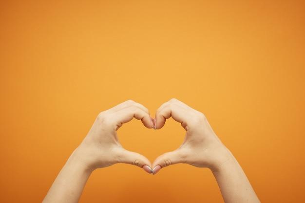 Gest kobiecej ręki trzymającej serce z jego palców