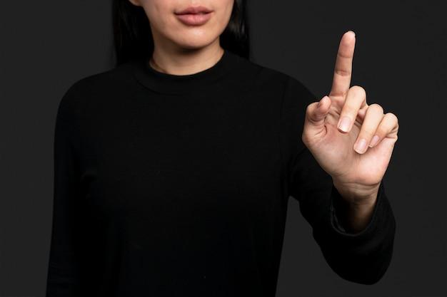 Gest kobiety naciskający na niewidoczny ekran