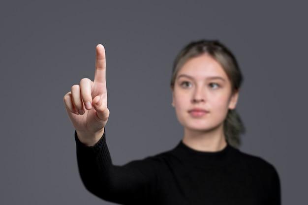 Gest kobiety naciskający na niewidzialny ekran